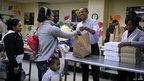 President Barack Obama and his mother-in-law Marian Robinson, right, distribute bags of food at Martha's Table, a Washington DC food pantry.