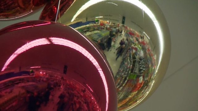 Supermarket aisles reflected in Christmas baubles