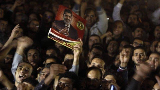 Demonstrators with poster of President Mursi