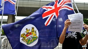 Protestors carrying colonial Hong Kong flags stand outside the Chinese liason office in Hong Kong on October 1, 2012