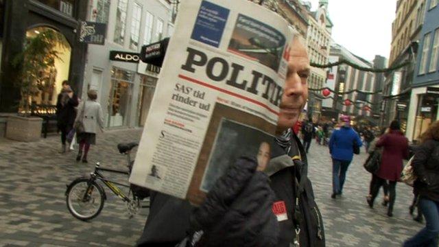 Man holds Danish newspaper