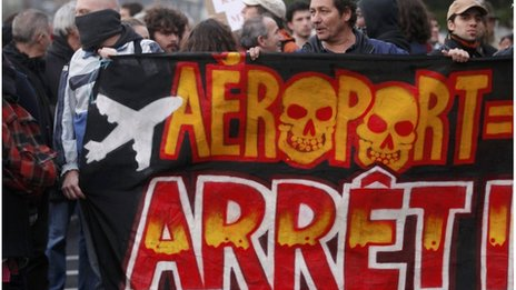 """Demonstrators hold a banner saying """"Airport, Stop"""" at a demonstration on Saturday"""