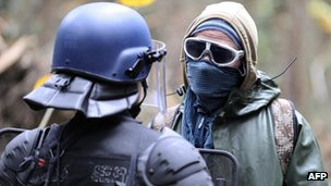 A riot policeman confronts a masked protester at the proposed site of the new airport on Saturday