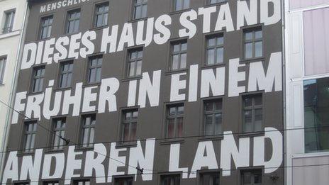 A building in Berlin's tech district with 'this house used to be in another country' painted on it