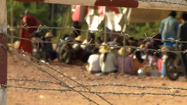 Seated protesters behind barbed-wire fence