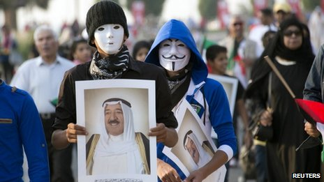 Youths wearing masks carry pictures of Kuwait's Emir during a celebration of the 50th anniversary of the constitution in Kuwait City (10 November 2012)