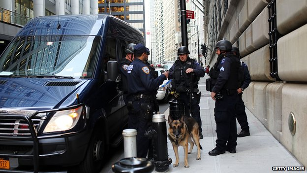 Police men and a police dog stand next to a police van