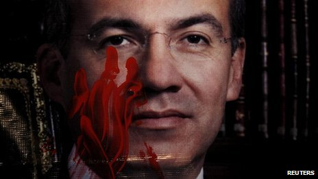 A photograph of Mexico's President Felipe Calderon is stained with paint to simulate blood, during a protest against his government, in power for six years, in Mexico City (28 November 2012)
