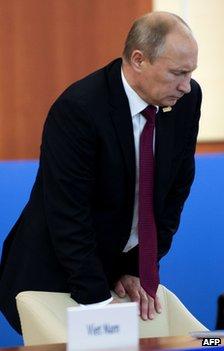 Russian President Vladimir Putin braces himself against a chair at a summit in Vladivostok, 9 September