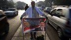 Morsi supporter holds a banner as protesters gather - 2 December 2012