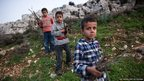 Khoder, 7, Salah, 7, and Yousef, 6, (left to right) collect firewood outside a former sheep shed in northern Lebanon, where they now live.