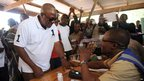 An electoral commission official checks the identification of President John Mahama in Bole. Photo: 7 December 2012