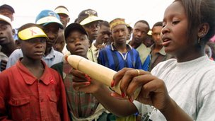 An educator shows how to use a condom in Nairobi, Kenya in December 2001, during International AIDS day.