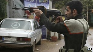 A Sunni gunman fires his weapon during clashes that erupted between pro and anti-Syrian regime gunmen in Tripoli, Lebanon, 5 Dec