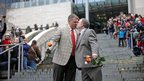 Brad and Jay McCanta kiss to a cheering crowd after getting married at Seattle City Hall