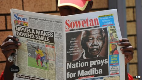 A man reads a newspaper with news about Nelson Mandela's health in Johannesburg (10 December 2012)