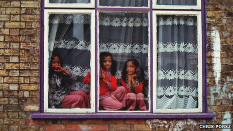 Girls from an Asian family play in the house window