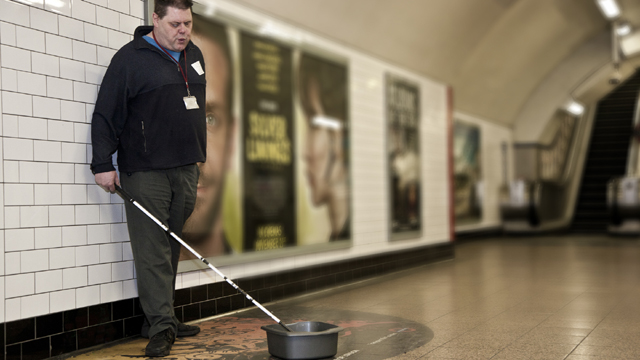 Mark busking with his cane and washing-up bowl