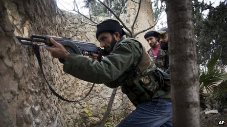 Syrian rebel fighters fire at a Syrian army position in Aleppo province (13 December 2012)
