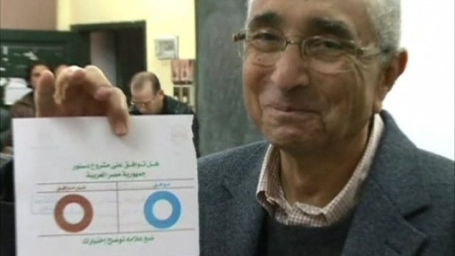 Man holding up his ballot paper