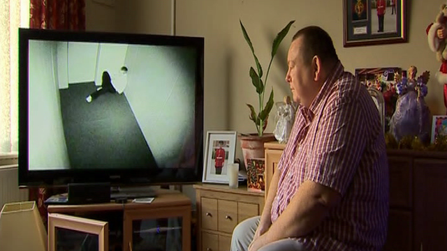 Andrew Parry yn gwylio DVD o'i fab mewn ystafell 'seibiant'
