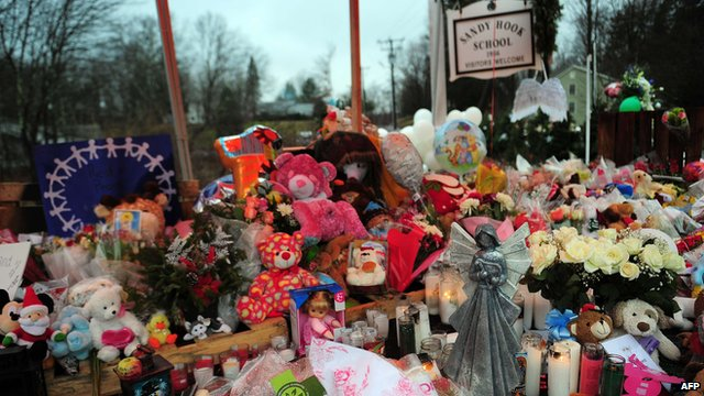 Flowers and tributes are placed in front of Sandy Hook School