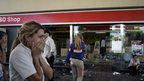 Employees of a looted petrol station react in San Fernando, Buenos Aires province on December 21