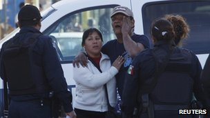 Relatives of a murdered policeman react at a crime scene in Ciudad Juarez, 9 December 2012