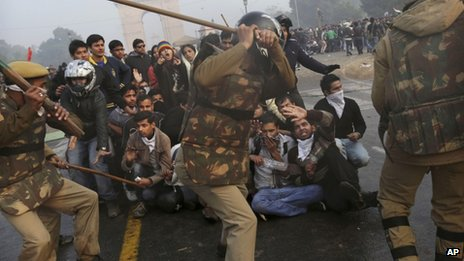 Protesters shield themselves as Indian police prepare to beat them with sticks during a violent demonstration near the India Gate against a gang rape and brutal beating of a 23-year-old student on a bus last week, in New Delhi, India, Sunday, Dec. 23, 2012.