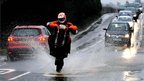 A motorcyclist tries to avoid a puddle on a road in Willington, Derbyshire.