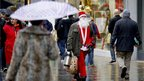 A man dressed as Santa Claus walks past shoppers in Market Street, Manchester