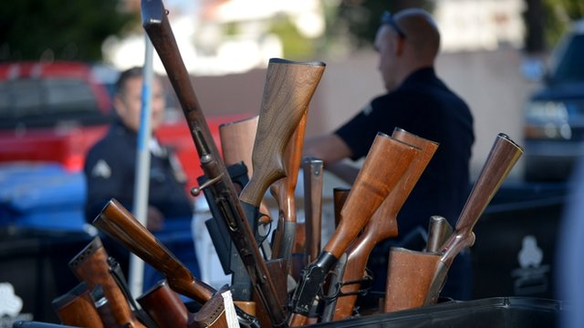 LAPD officers collect guns during the LAPD Gun Buyback Program event in Van Nuys area, north Los Angeles