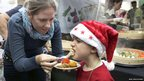 A woman feeds her son, dressed in a Father Christmas hat (photo credit: Ariel Jerozolimski)