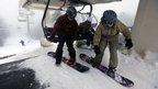 Snowboarders step off a chairlift at Wachusett Mountain Ski Area, in Princeton, Massachusetts 27 December 2012