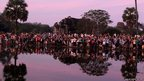 Tourists gather to watch and take pictures of Cambodia's world famous Angkor Wat temple