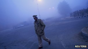 Guard outside the funeral ground in Delhi, India (30 Dec 2012)