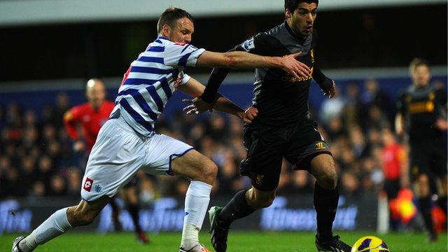 Liverpool's Luis Suarez (r) glides past QPR's Clint Hill