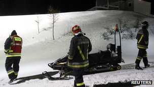 Rescue workers take part in an operation to recover bodies of tourists in Val di Fiemme, northern Italy.