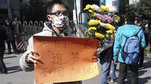 """A man wearing a mask with the word 'Silent' holds a banner reading: 'Let""""s chase our dreams together, go Southern Weekly newspaper' during a protest outside the headquarters of the newspaper in Guangzhou, Guangdong province"""