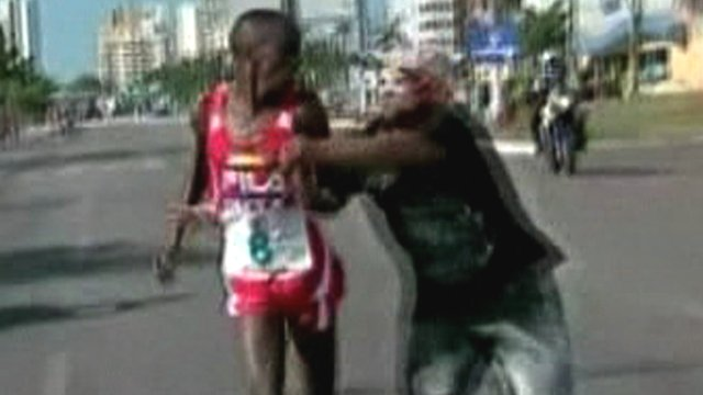 Spectator tackles runner during race