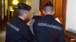 French police guard a defendant at an earlier appearance in the trial in Paris, 3 December