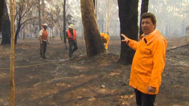 Nick Bryant looking at burned landscape