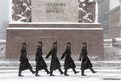 Honour guards march near the Freedom Monument during a snowfall in Riga