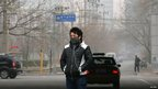 A man wearing a face mask stands on a street on a hazy winter day in central Beijing January 13, 2013