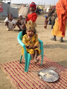 Child dressed as Hindu god sits in front of plate with money on it
