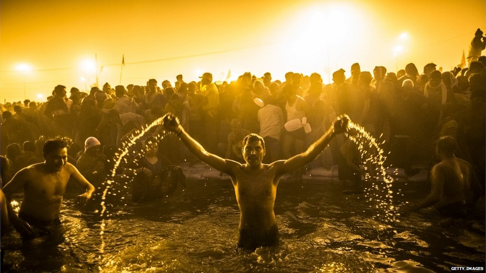 Hindu devotees bathe in the waters of the Ganges river during the auspicious royal bathing day of Makar Sankranti, the start of the Maha Kumbh Mela, in Allahabad, India, 14 January 2013