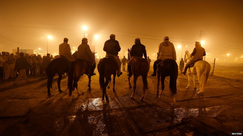 Mounted policemen patrol during the first grand bath in Allahabad, 14 January 2013
