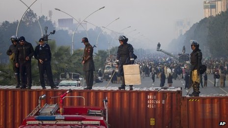 Pakistani police officers stand guard atop shipping containers while supporters of Pakistan Sunni Muslim cleric Tahir-ul-Qadri stage an anti government rally in Islamabad, Pakistan on Tuesday, Jan. 15, 2013.