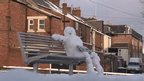Snowman sitting on park bench reading newspaper