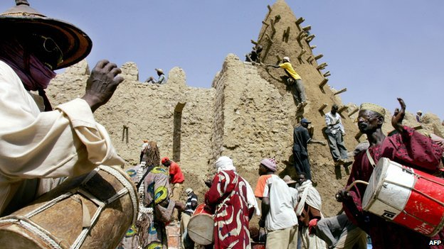 Archive shot from 2006 of residents of Timbuktu encouraging workers restoring the City of 333 Saints' Great Mosque